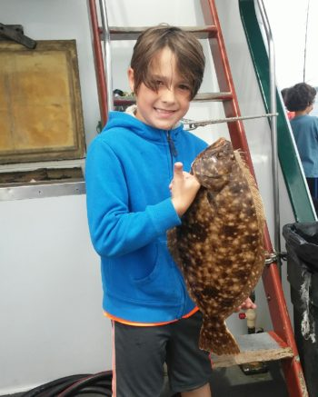 "Noah Blasi of Warwick with the 22"" summer flounder (fluke) he caught at the RI Saltwater Anglers Association fishing camp."