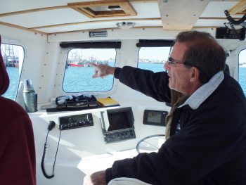 Capt. Charlie Donilon at the helm on Snappa, his charter vessel, where he and his clients have caught, tagged and released over 2500 sharks.