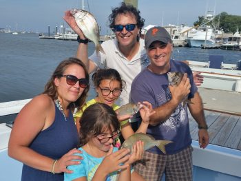 Mikele St.-Germain, daughters Eva and Francesca, husband Pierre and friend Steve Brustein (back row) enjoyed scup fishing last summer. The scup, an underutilized species, were cooked on the grille for dinner.