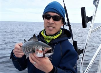 """Jamie Wong of Cambridge, MA with a 21"""" bonito caught in November off Newport, RI. Climate change has brought warm water bait and fish to the region for longer periods of time."""