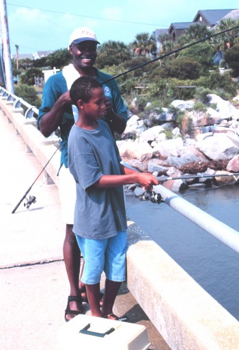 Father and Son Fishing From a Bridge