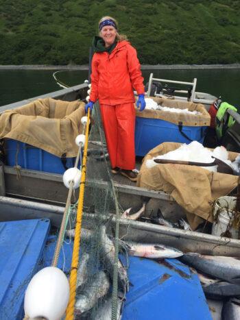 Theresa in the skiff picking setnet salmon